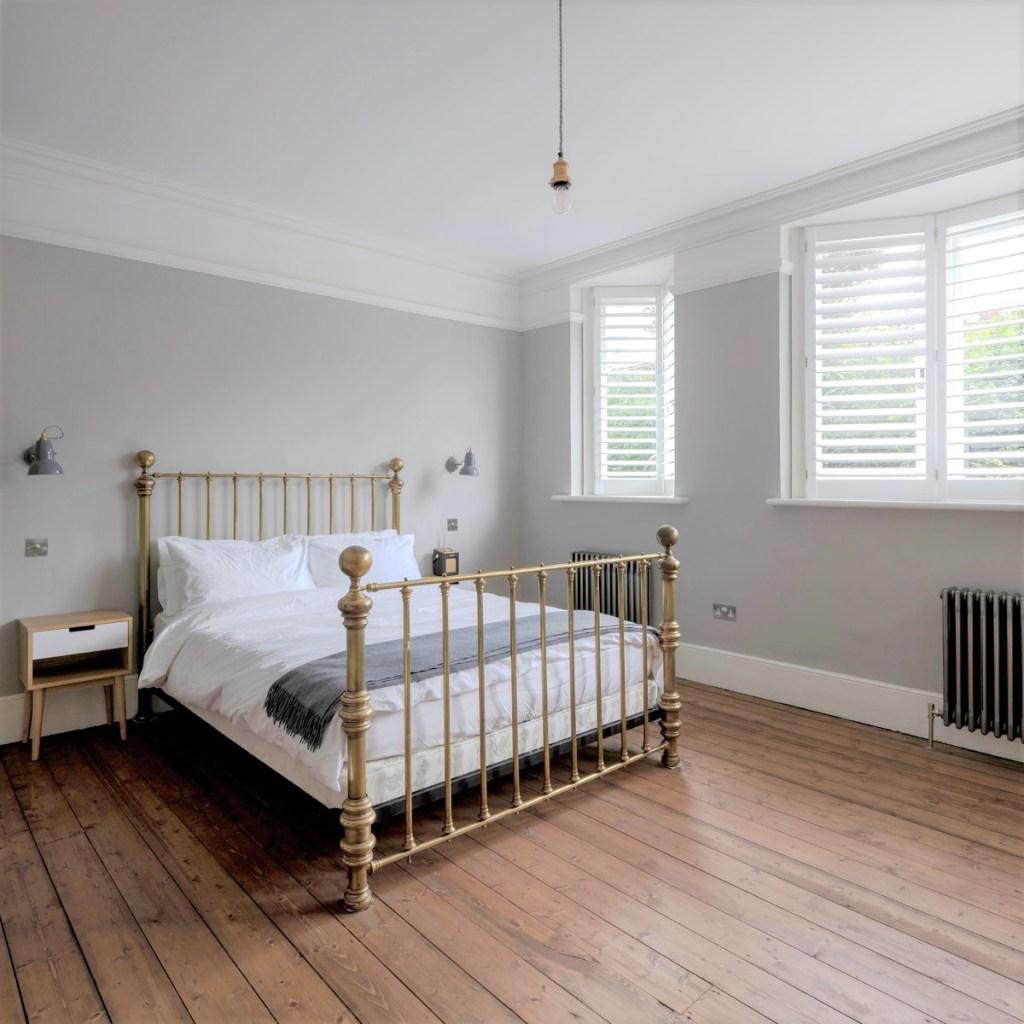 Quarto com piso de tábuas de madeira. Cama de casal com lençol branco.