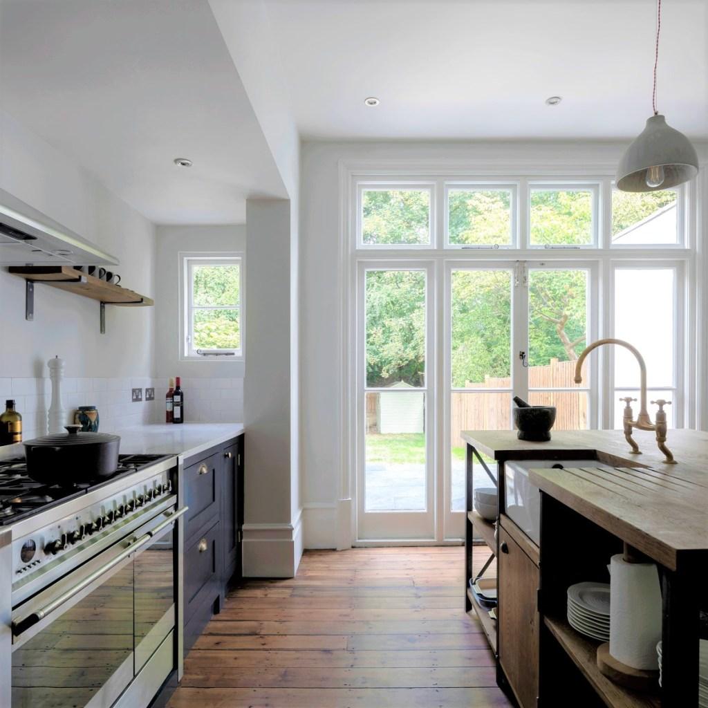 Cozinha com piso em madeira e ilha em madeira. Armários azul escuro. Porta em vidro para o jardim