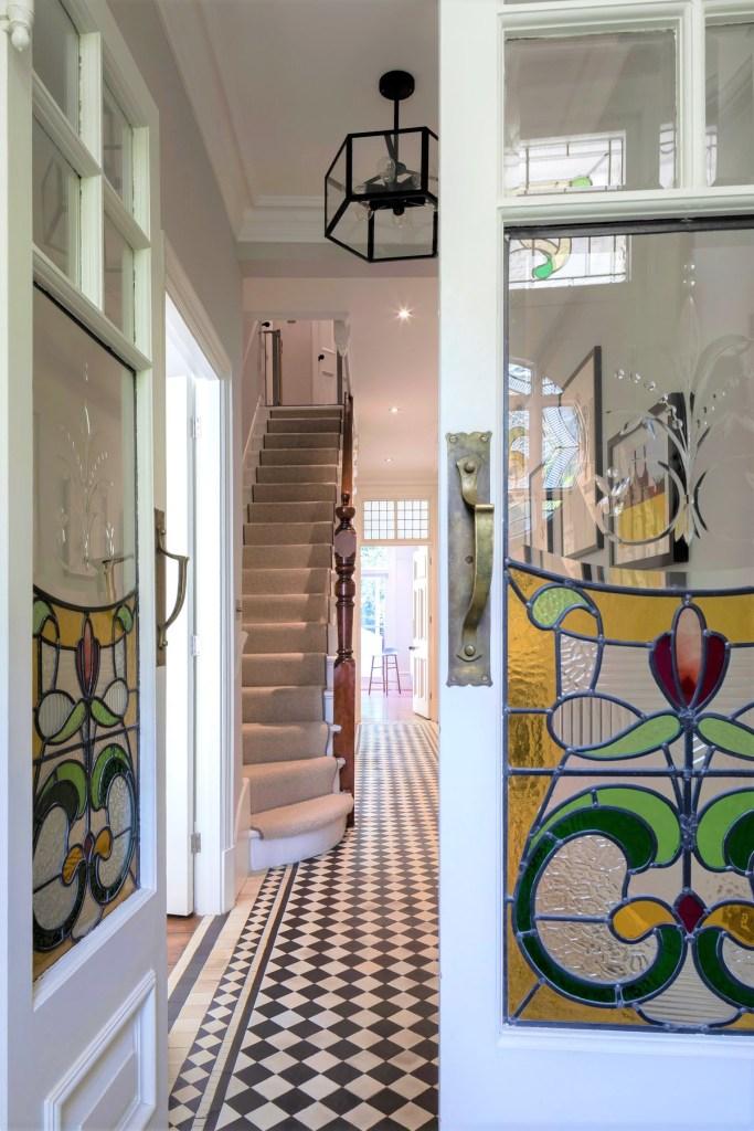 Porta com vitral amarelo, verde e vermelho com padrão de flor. Escadaria ao fundo.