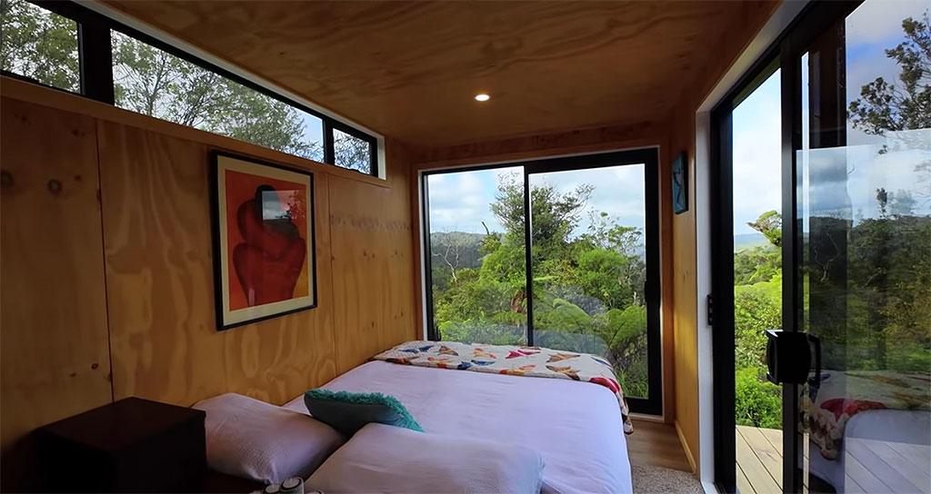 Quarto com cama de casal. Paredes e teto revestidos em madeira. Vista para a floresta