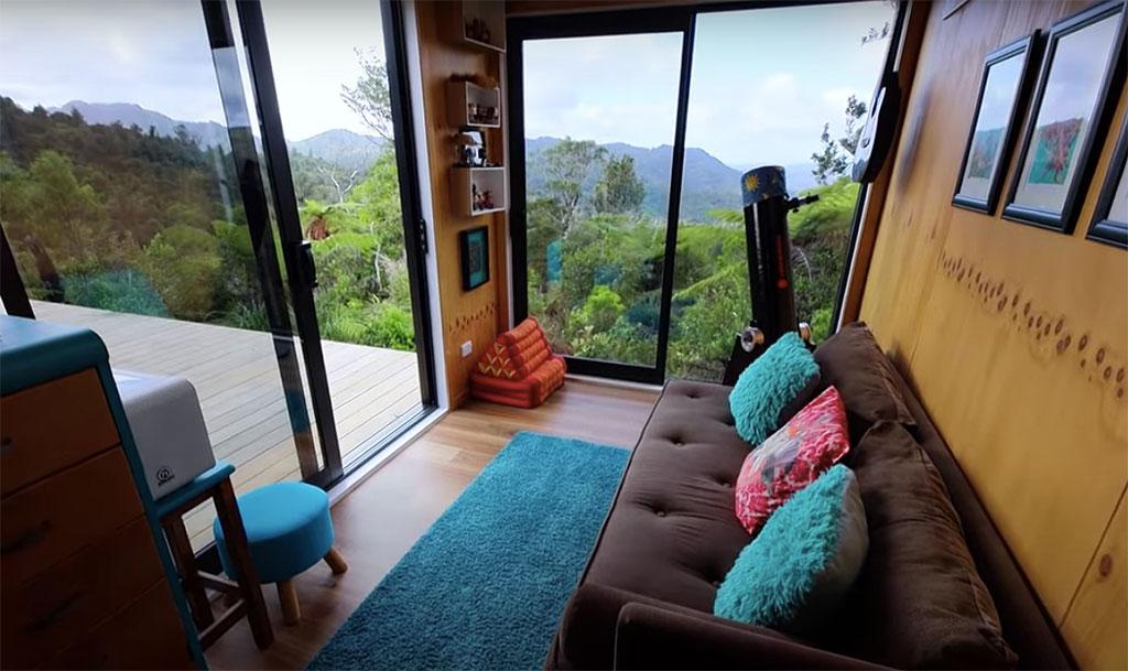 Pequeno estar com sofá marrom com almofadas azuis voltado para deck de madeira.