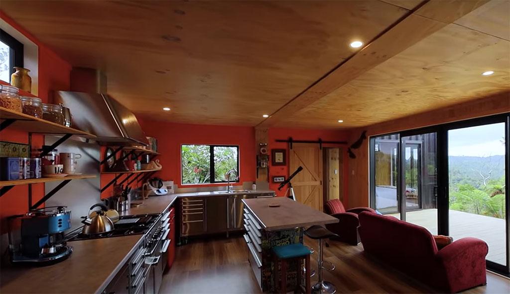 Cozinha integrada com estar. Parede vermelha. Piso e teto revestidos em madeira. Sofá vermelho voltado para a janela
