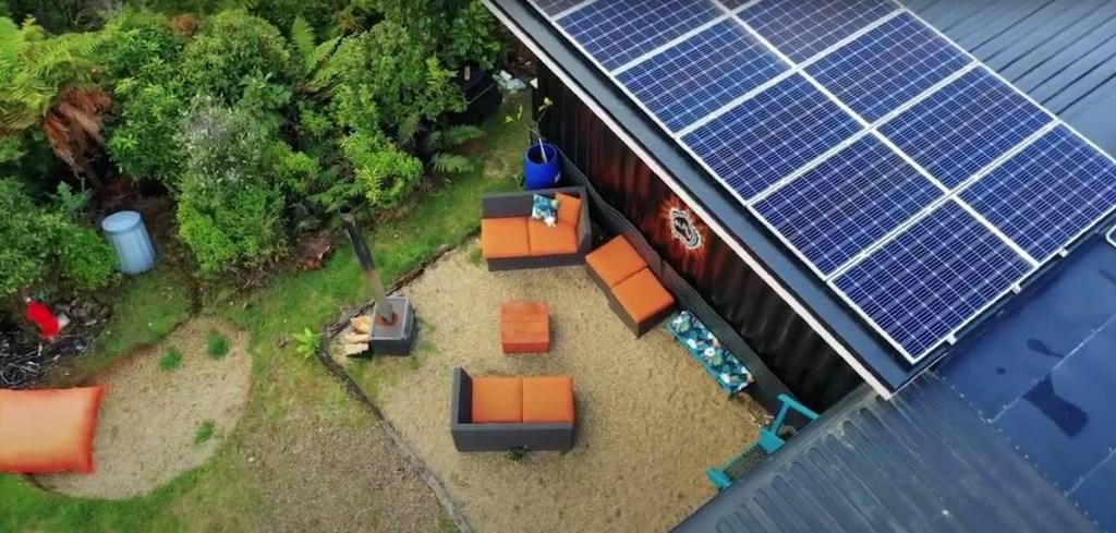 Foto aérea do fundo da casa com espaço de convivência com sofás e horta