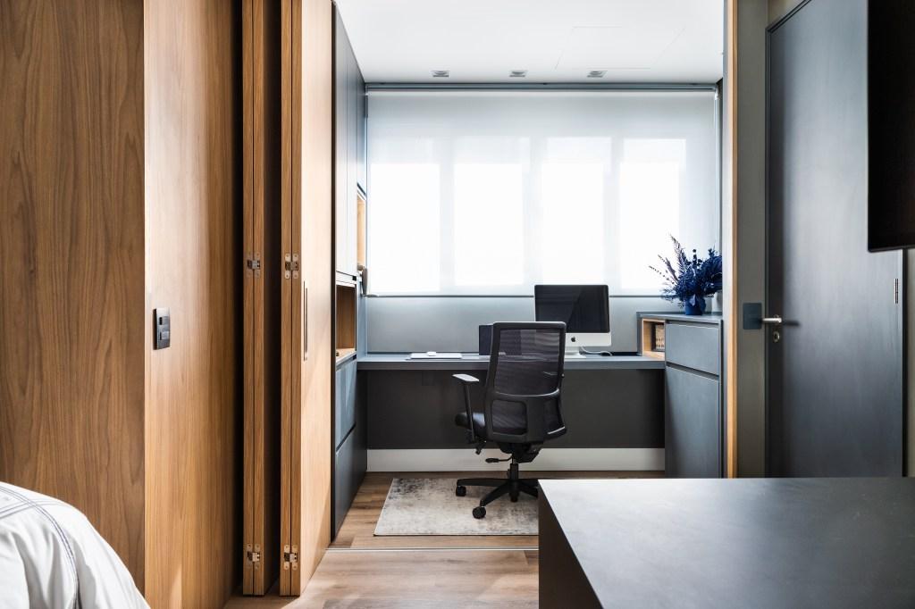 Escritório no quarto do casal, com porta camarão para fechar o espaço após o uso. A madeira clara da porta combina com os móveis e parede escura
