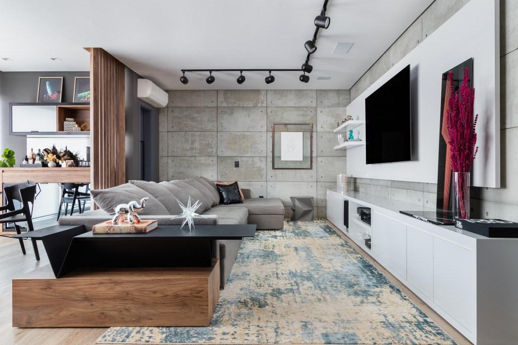 Sala de estar da Casa Vila Mariana, com moveis brancos, cinza e madeira. No chão, porcelanato e na parede, revestimento de cimento queimado