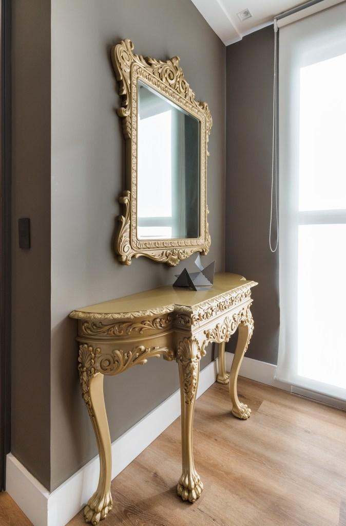 Aparador dourado na casa vila mariana, com um espelho com moldura na mesma cor, preso a uma parede cinza escuro