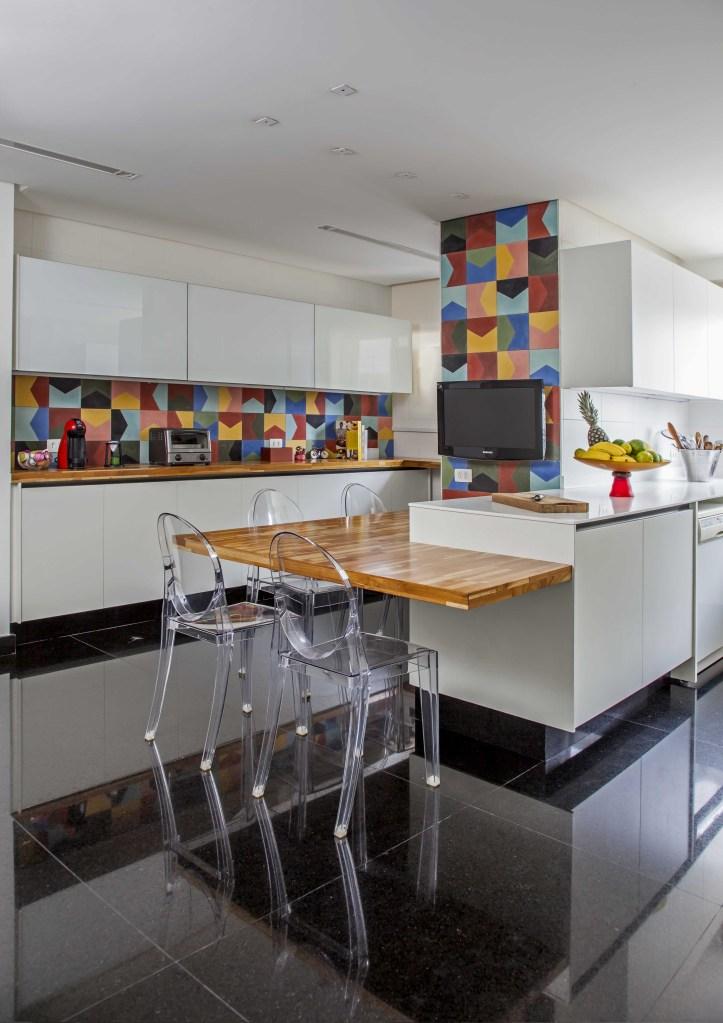 Cozinha com piso escuro, bancada de madeira com cadeira de acrilico e backsplash de ladrilhos coloridos