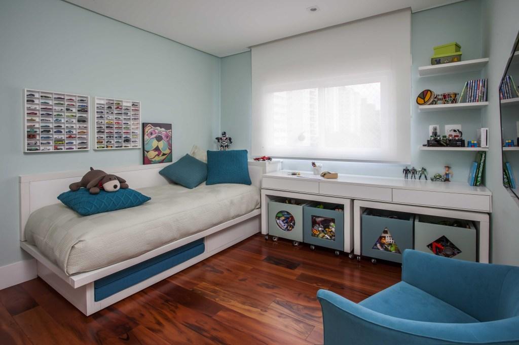 quarto com piso de madeira, cama com roupa cinza e almofada azuis