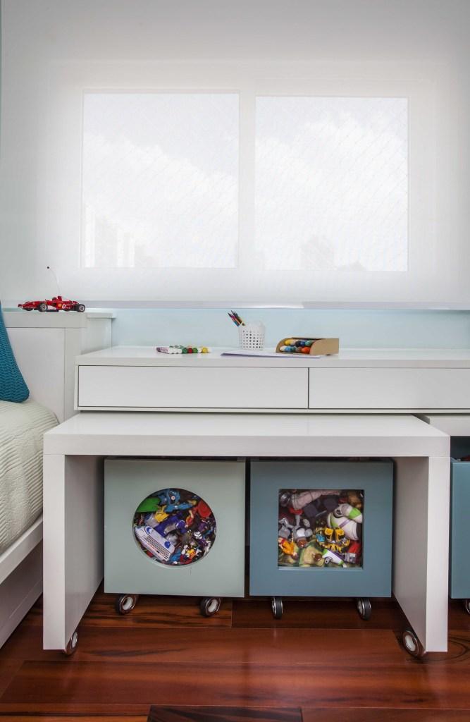 Detalhe do quarto, duas caixa organizadora de brinquedos embaixo da mesa branca encaixada no banco branco