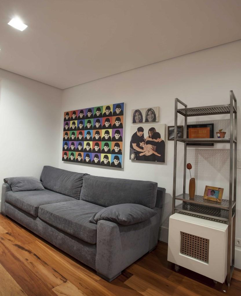 Sala de estar com sofá cinza, estante com proteção na preteleira debaixo. Na parede, quadro com padrão de rostos com fundo colorido, estilo artpop