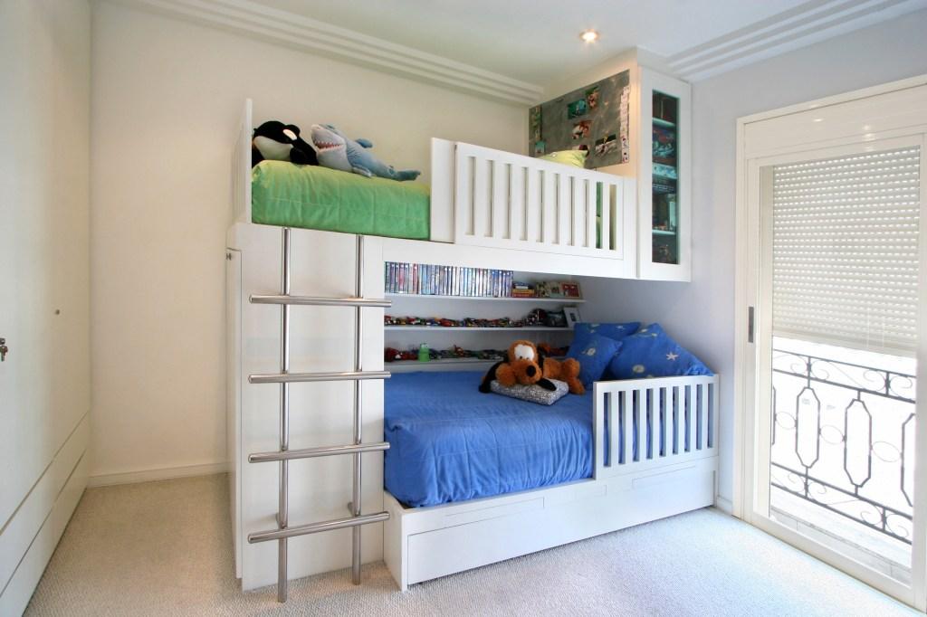 Quarto com beliche branca, com escada do lado esquerdo. A cama de baixo tem roupa azul, enquanto a de cima tem roupa verde