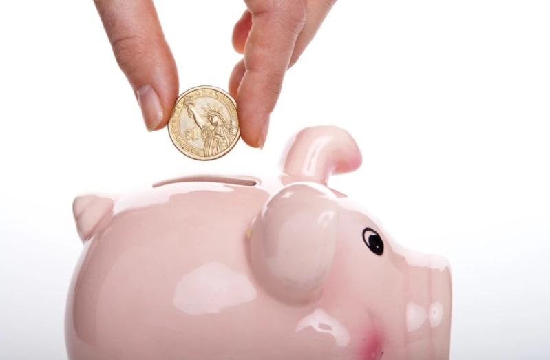 Cofre de porquinho rosa com moeda sendo colocada