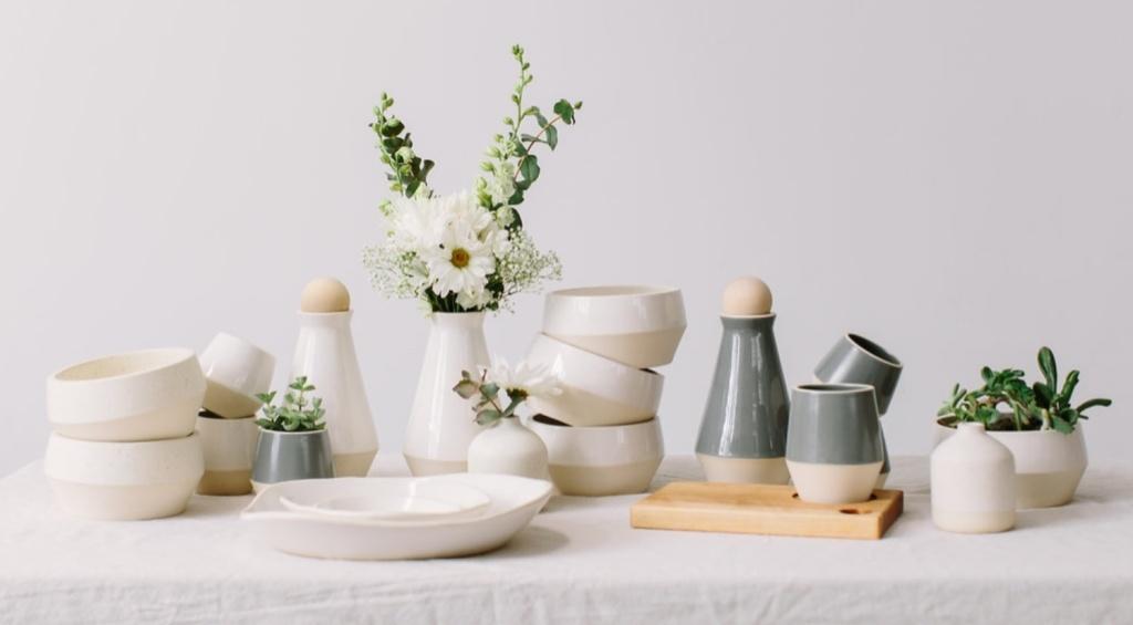 Mesa com pratos, copos e tigelas em cerâmica branca. Pequenas folhas e flores nos vasos.