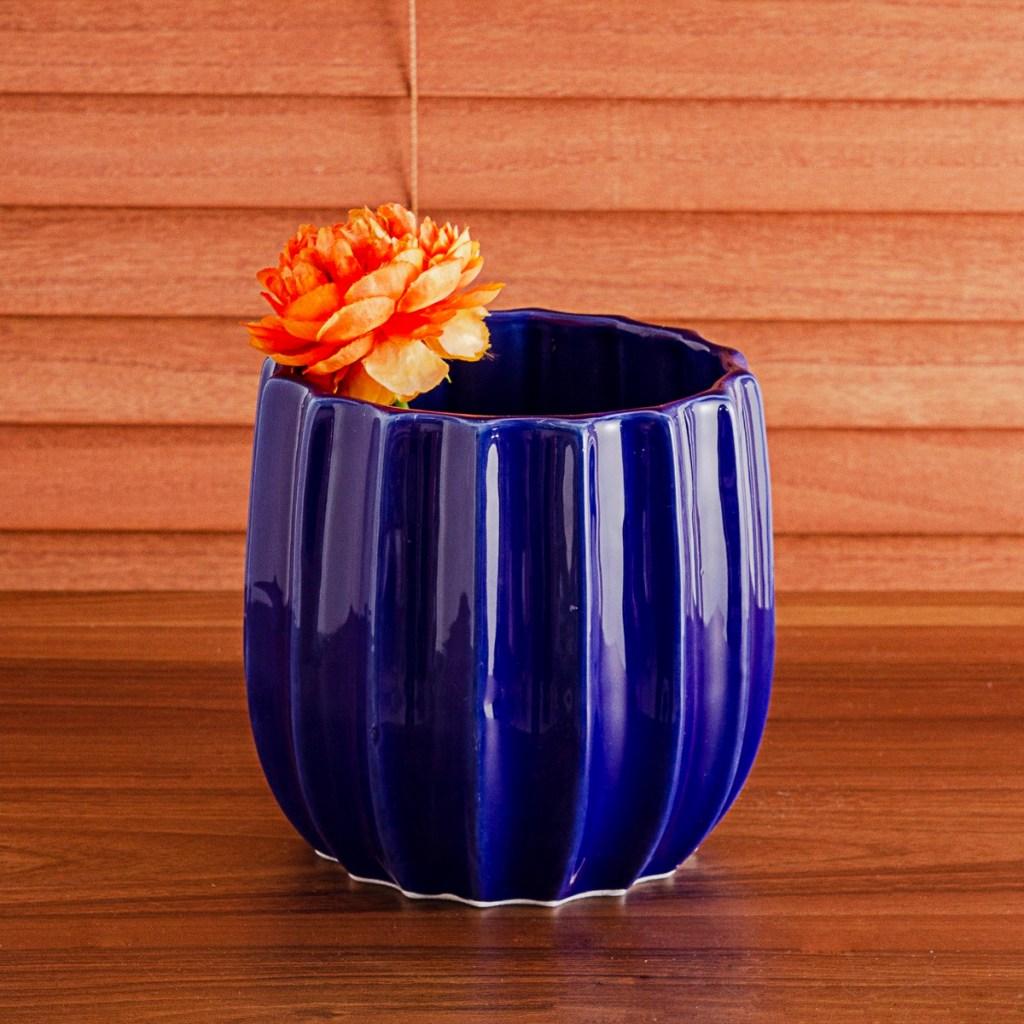Vaso de cerâmica azul, com flor laranja sobre bancada de madeira