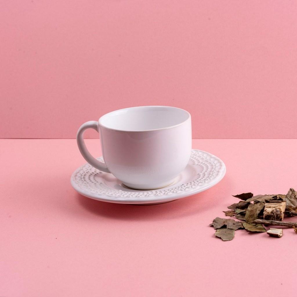 Xícara e pires brancos de cerâmica, em fundo rosa, com cascos de arvores ao lados