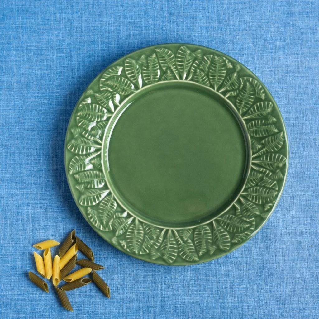 Prato raso de cerâmica verde, com desenhos de folhas na borda, em fundo azul mesclado com grãos de macarrão