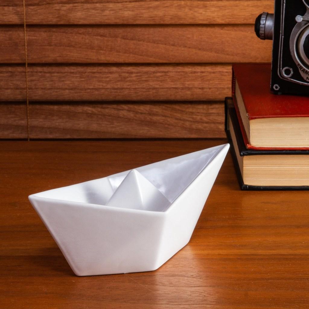 Barco de papel de cerâmica, sobre bancada de madeira com livros e máquina fotográfica antiga ao fundo