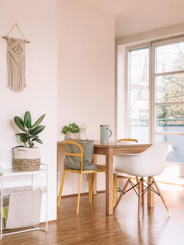 Mesa pequena com uma cadeira em madeira e uma cadeira Eams branca. Paredes rosa claras