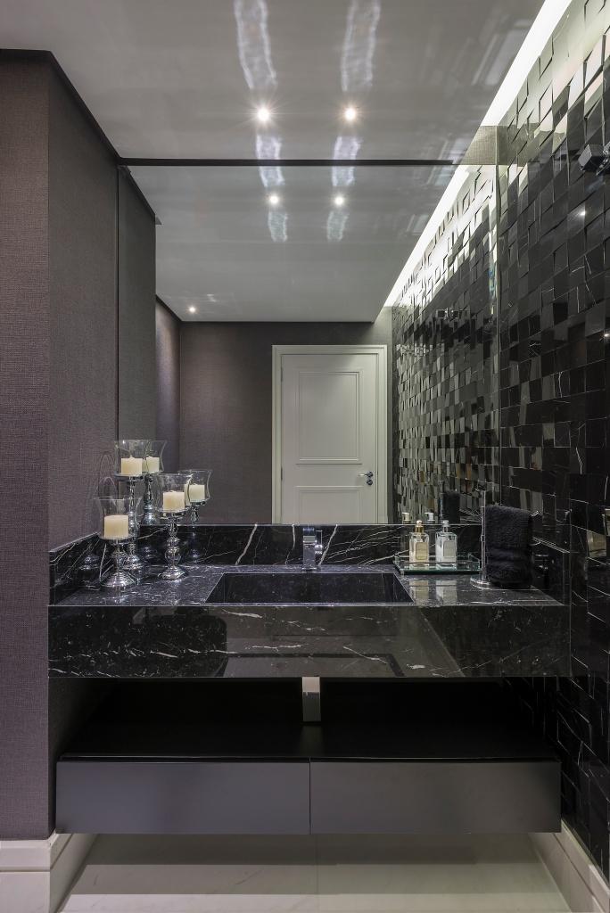 Banheiro com pedras pedras e texturizadas. No teto, o forro de drywall é vazado por conta da iluminação