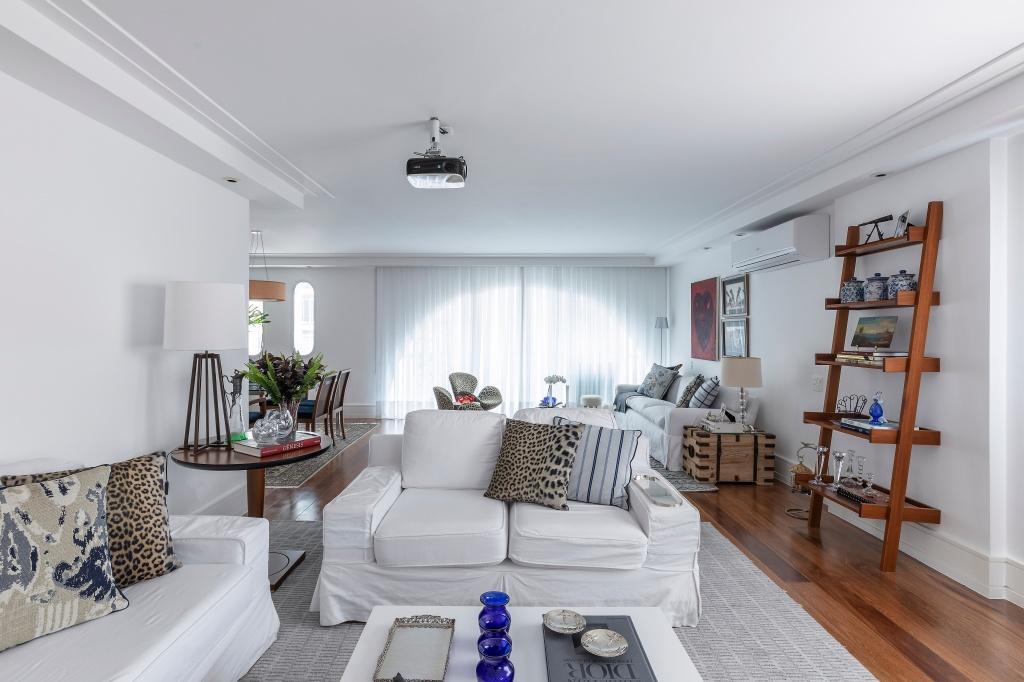 Sala de estar com sofás e paredes brancas, com forro em gesso nas laterais por conta da iluminação. No chão de madeira, uma tapete cinza decora o espaço, assim como almofadas estampadas. Um mesa de centro, de lateral e uma estante completam o ambiente