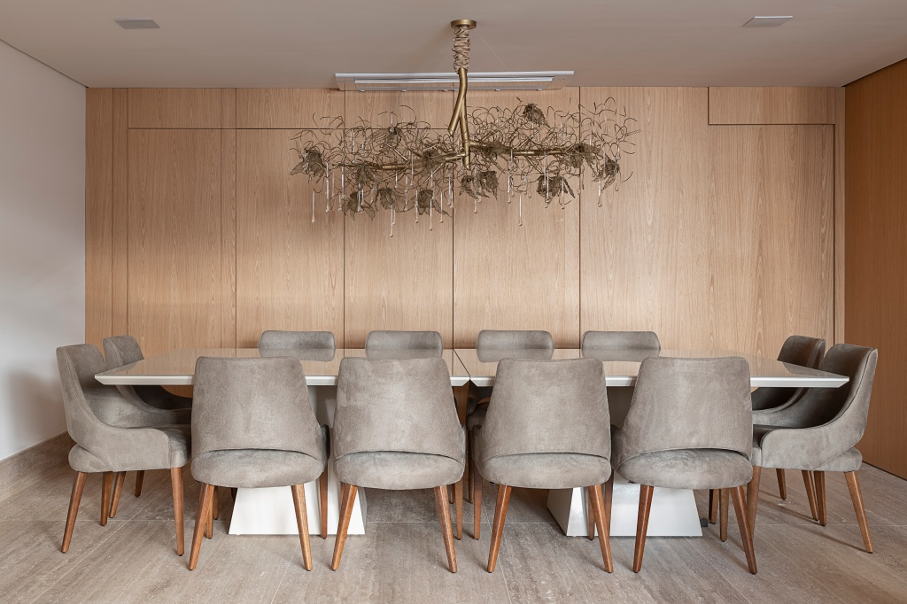 Sala de jantar com mesa de doze lugares, com pendente acima da mesa. Forro de drywall, piso de madeira, assim como os armários na parede do cômodo