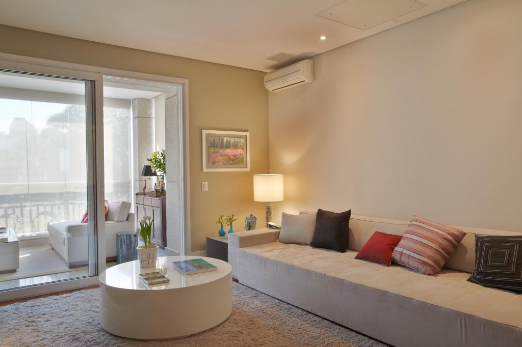 Sala de estar com sofá na cor creme, com tapete grande felpudo no chão e mesa de centro circular sólida. O forro no teto é na cor branca, com aparelhos de som e iluminação embutidos