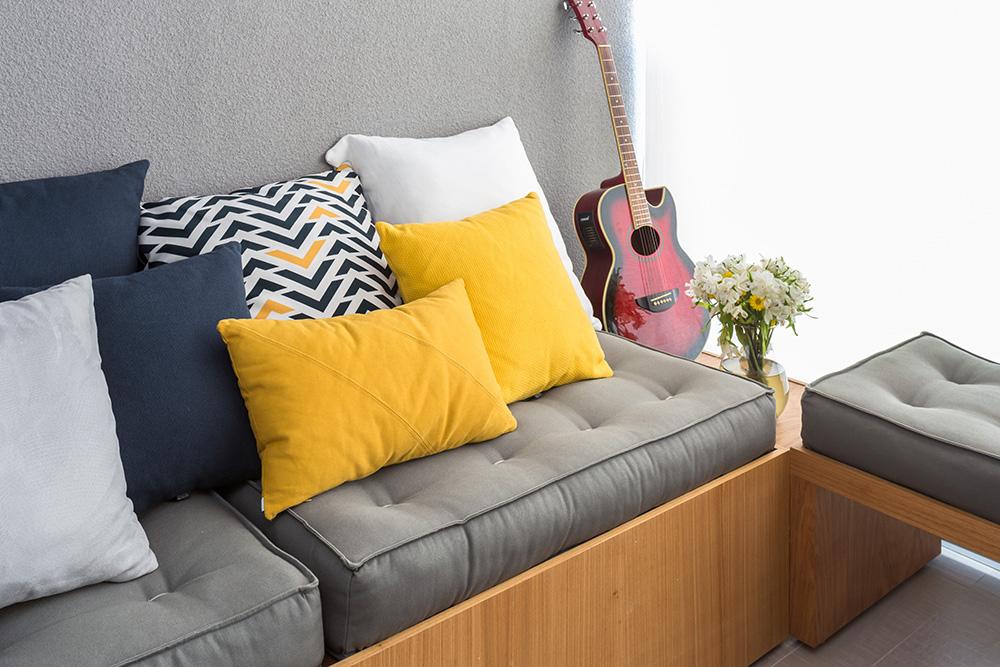 """Varanda com sofá. Almofadas azuis escuro, amarelas, brancas e uma com padrão em """"v"""" azul e amarelo. Violão vermelho no canto."""