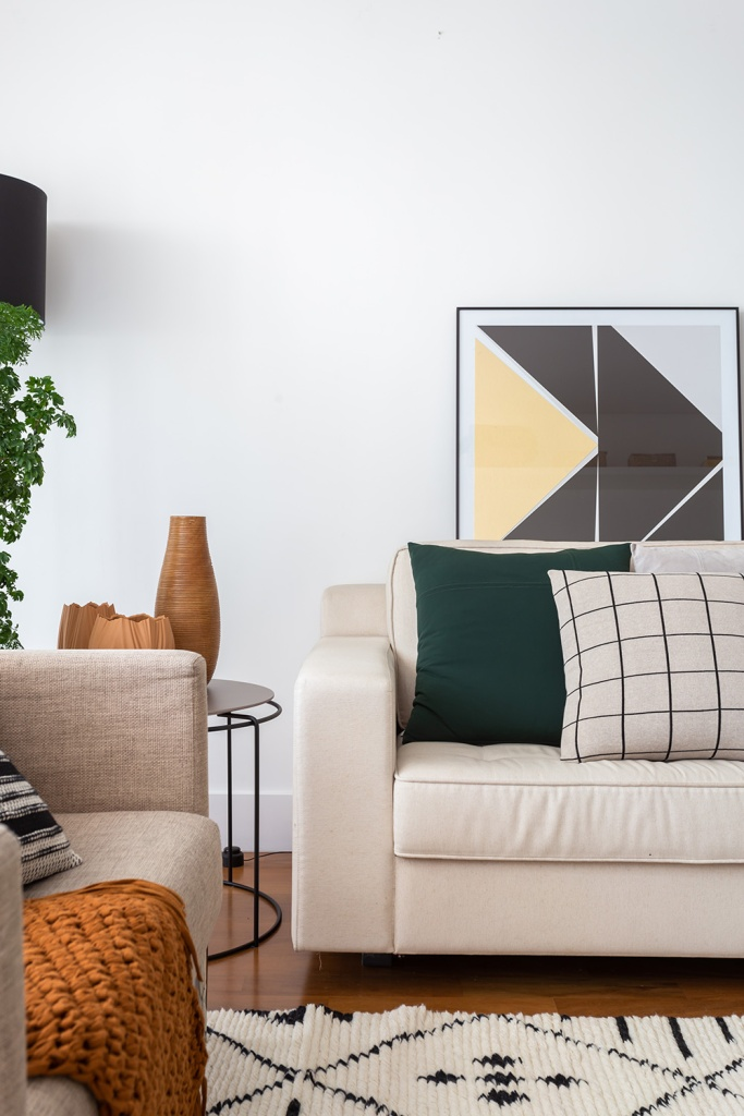 Sofá off-white com uma almofada verde escura e outra branca com listras pretas. Quadro geométrico ao fundo.