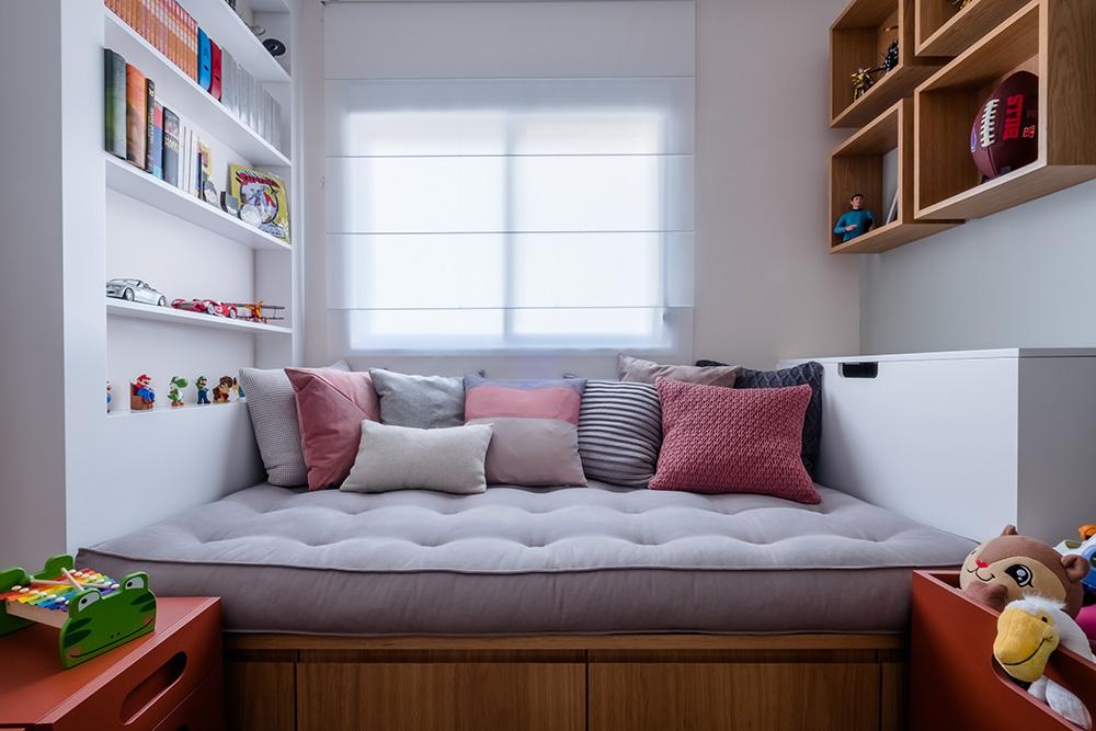 Quarto de criança com sofá cama com várias almofadas vermelhas e cinza claros.