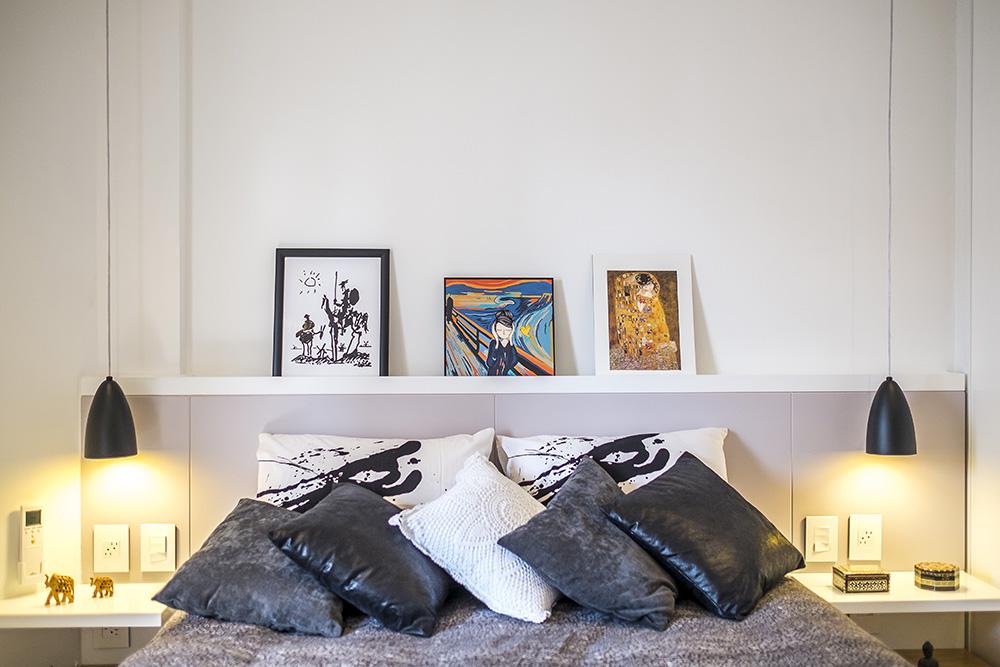 Cama com cinco almofadas pretas, cinzas e branca. Ao fundo, dois travesseiros brancos com grafismos pretos. Sobre a cabeceira, três quadros.