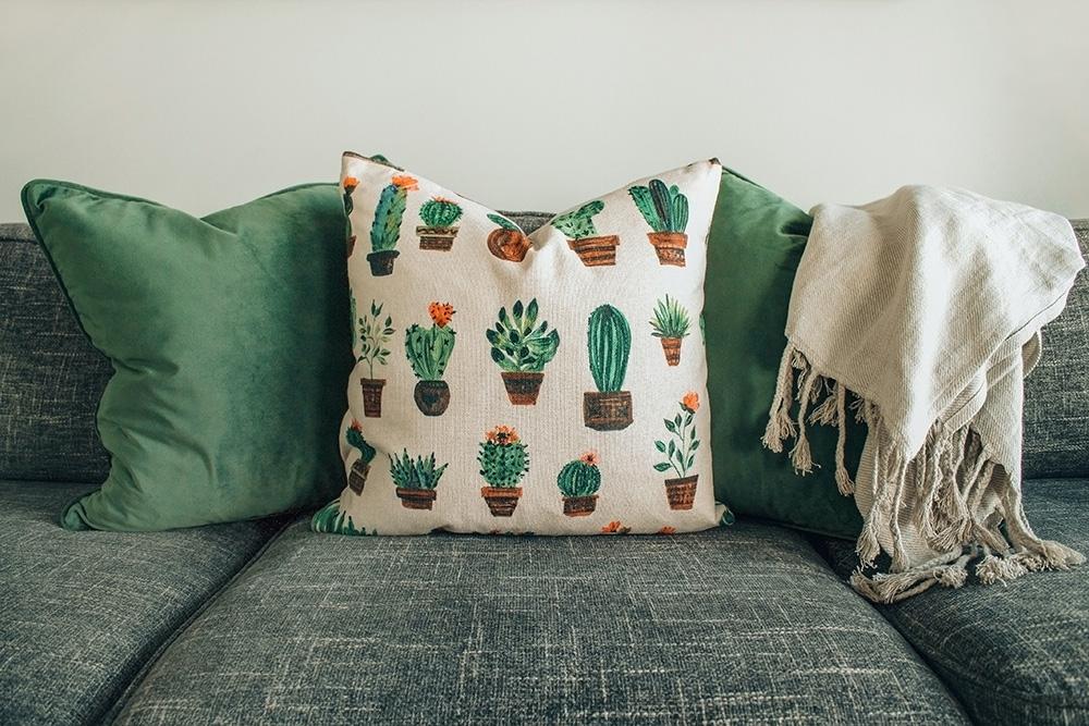 Sofá verde com três travesseiros: dois verdes lisos e um branco com estampa de cactus.