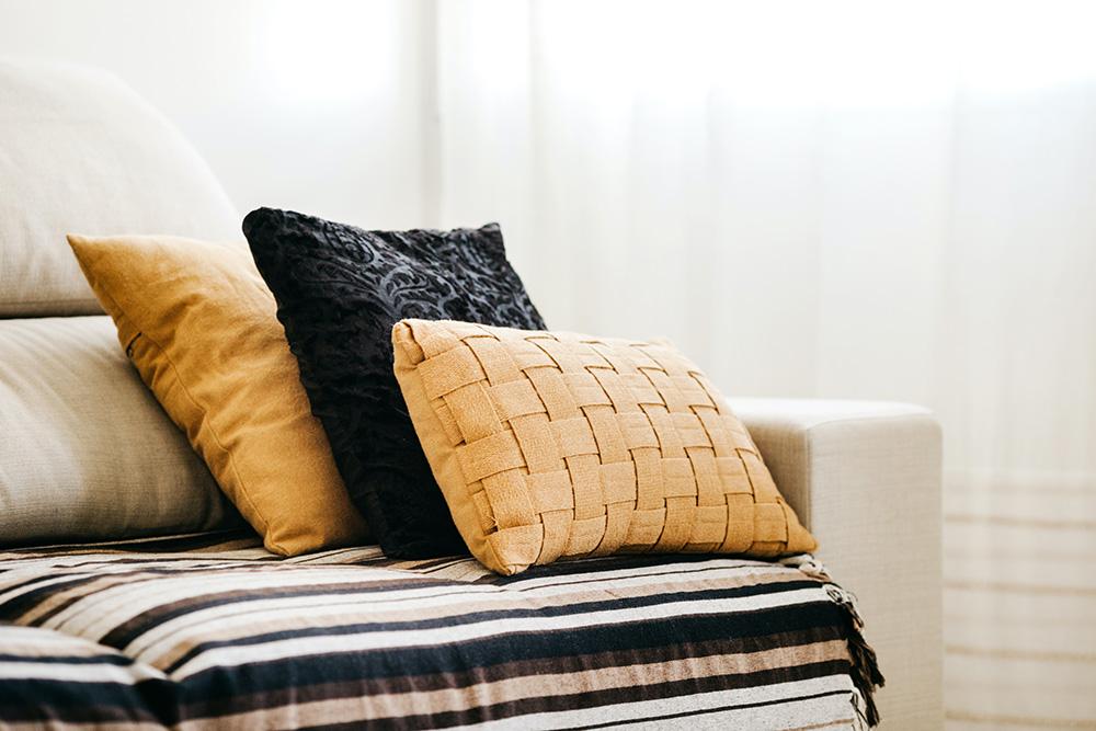 Sofá branco com manta branca e preta. Três almofadas, duas amarelas queimado e uma preta com textura