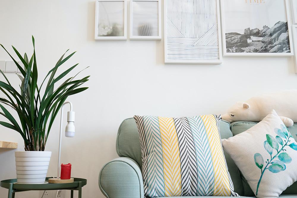 Sofá azul claro com travesseiro listrado de verde, amarelo e preto. Outro travesseiro com um ramo de folhas estampada. Pelúcia de urso polar. Ao lado, mesa de apoio verde escuro com vaso de folhagem.
