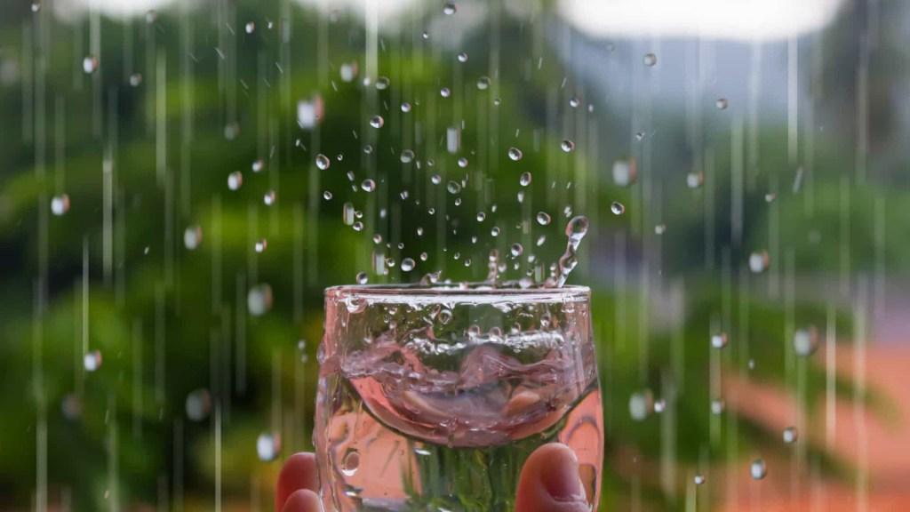 Mão segurando copo transparente em vidro armazenando água da chuva