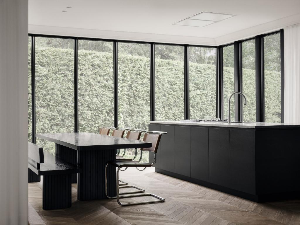Sala de estar com janelas grandes que cobrem as paredes. Vista para jardim. Mesa e bancada preta. Piso em madeira