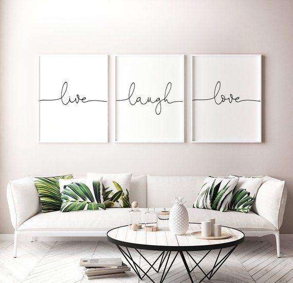 Living com sofá branco grande e almofadas com estampa de folhas. Na parede, quadros com as palavras Live Laugh e Love