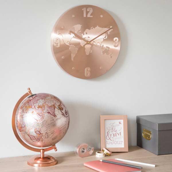 Mesa de escritório com globo, porta retrato com frase e relógio em metal rosé.