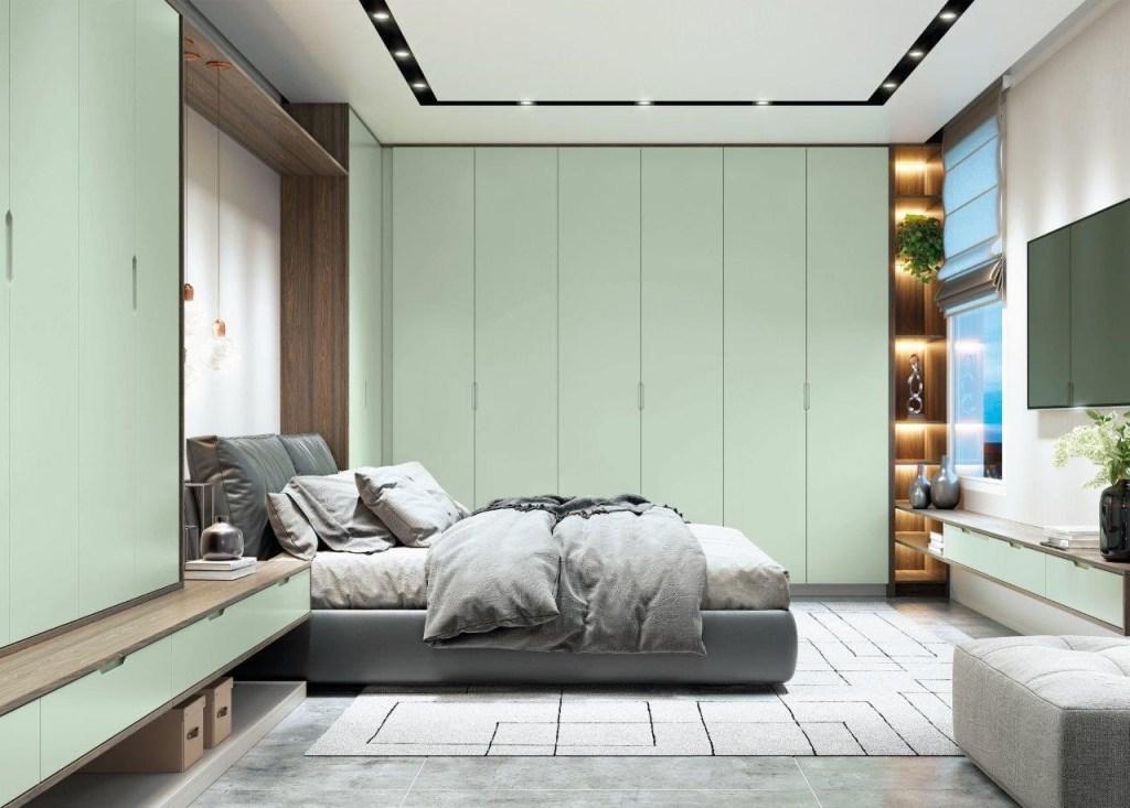 Quarto com piso de cimento queimado, com armários na cor verde claro