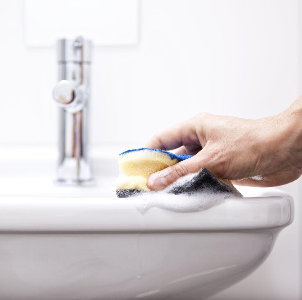 Mão limpando pia branca com esponja amarela