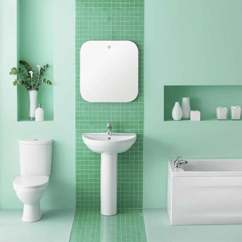 Banheiro verde claro vibrante com vaso sanitário, pia e banheira brancos