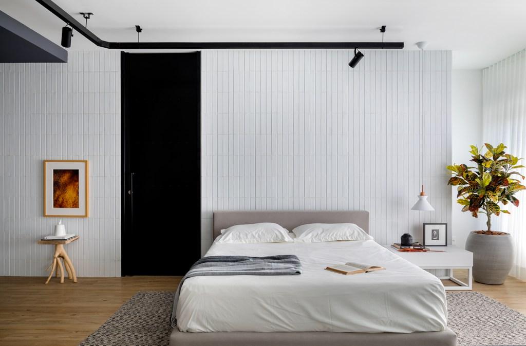 Quarto de casal, com cama baixa, em piso de madeira com tapete. Paredes brancas, com uma porta na cor preta