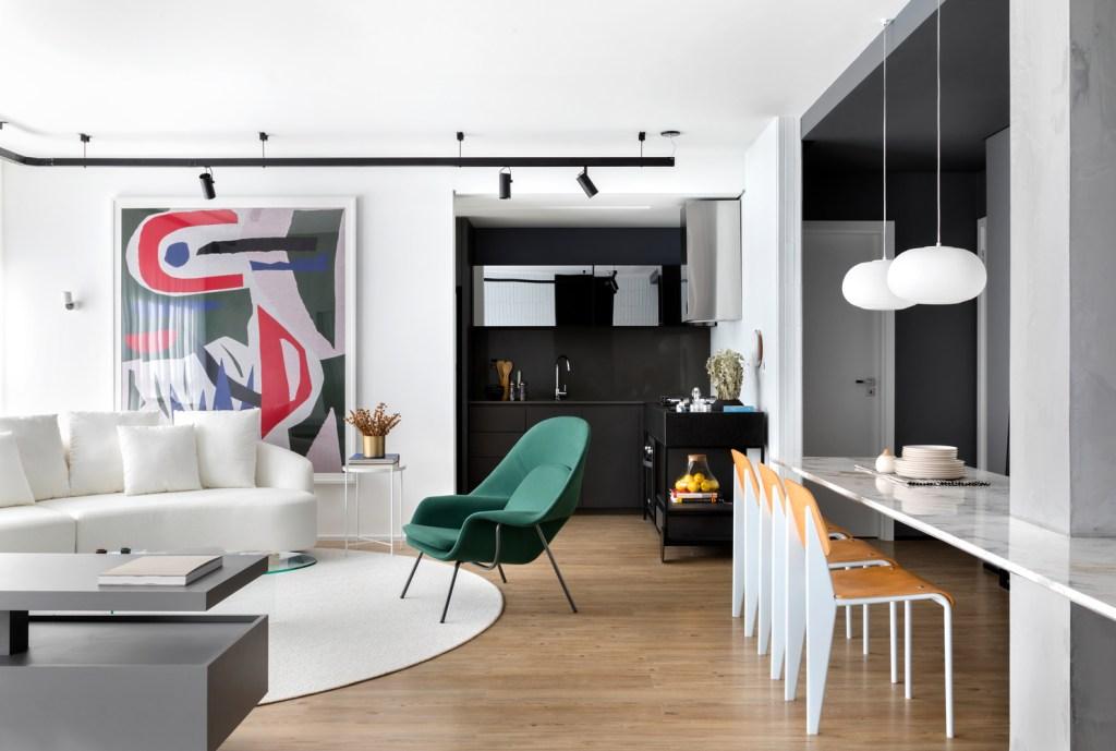 Sala de estar com piso de madeira,com tapete redondo branco no centro,sob sofá da mesma cor. Ao lado, uma poltrona verde, com uma mesa de janta branca, com detalhes em madeira. no teto, trilho de holofotes e na parede, uma obra de arte abstrata