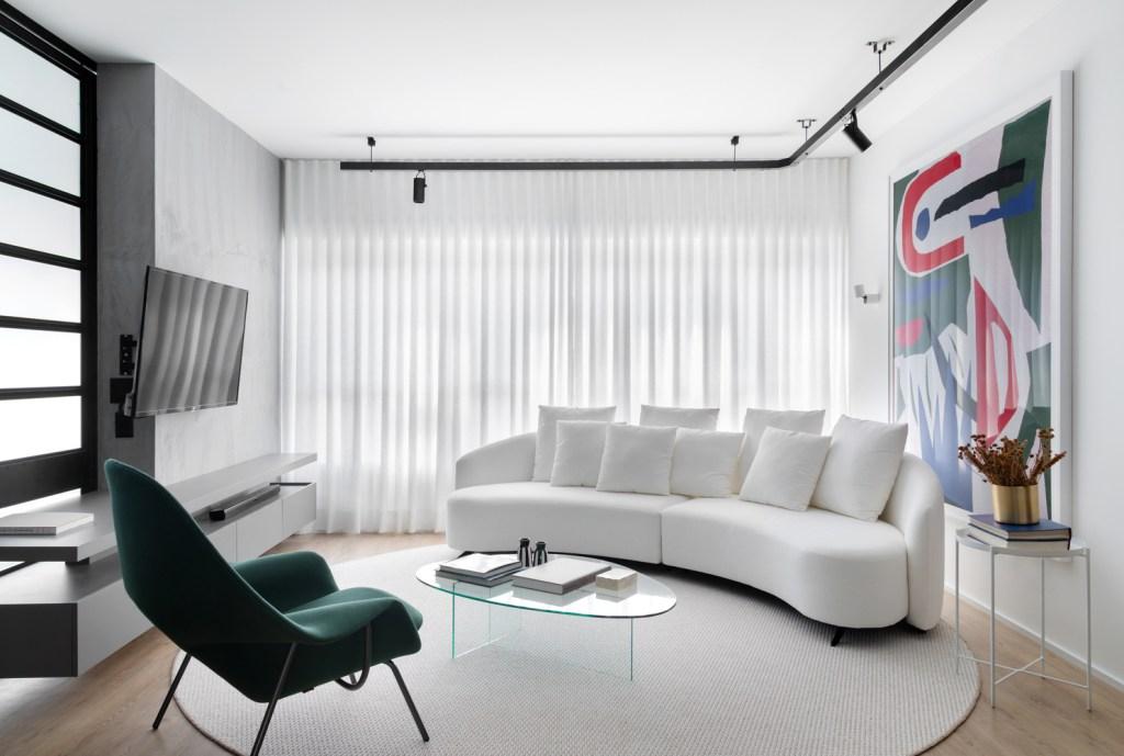 Sala de estar com piso de madeira e tapete redondo branco. O sofá, na mesma cor, é curvo e acompanha o movimento do tapete