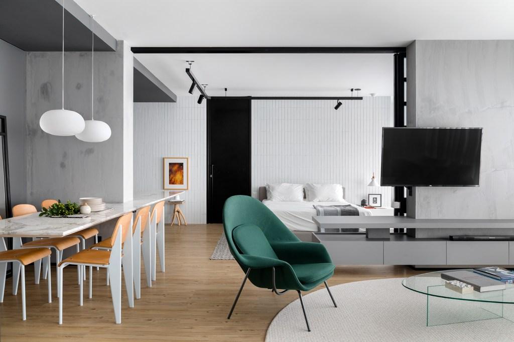 Sala de estar com piso de madeira,com tapete redondo branco no centro,sob sofá da mesma cor. Ao lado, uma poltrona verde, com uma mesa de janta branca, com detalhes em madeira. Ao fundo, a porta de correr aberta mostra as áreas social e íntima integradas