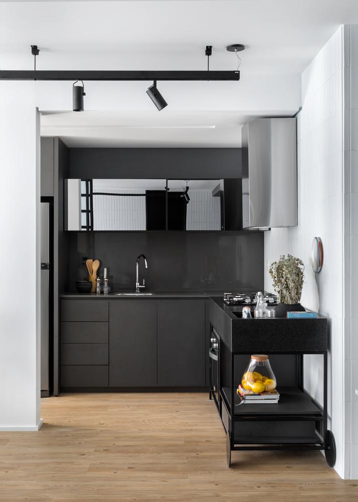 Cozinha com armários pretos e espelhados