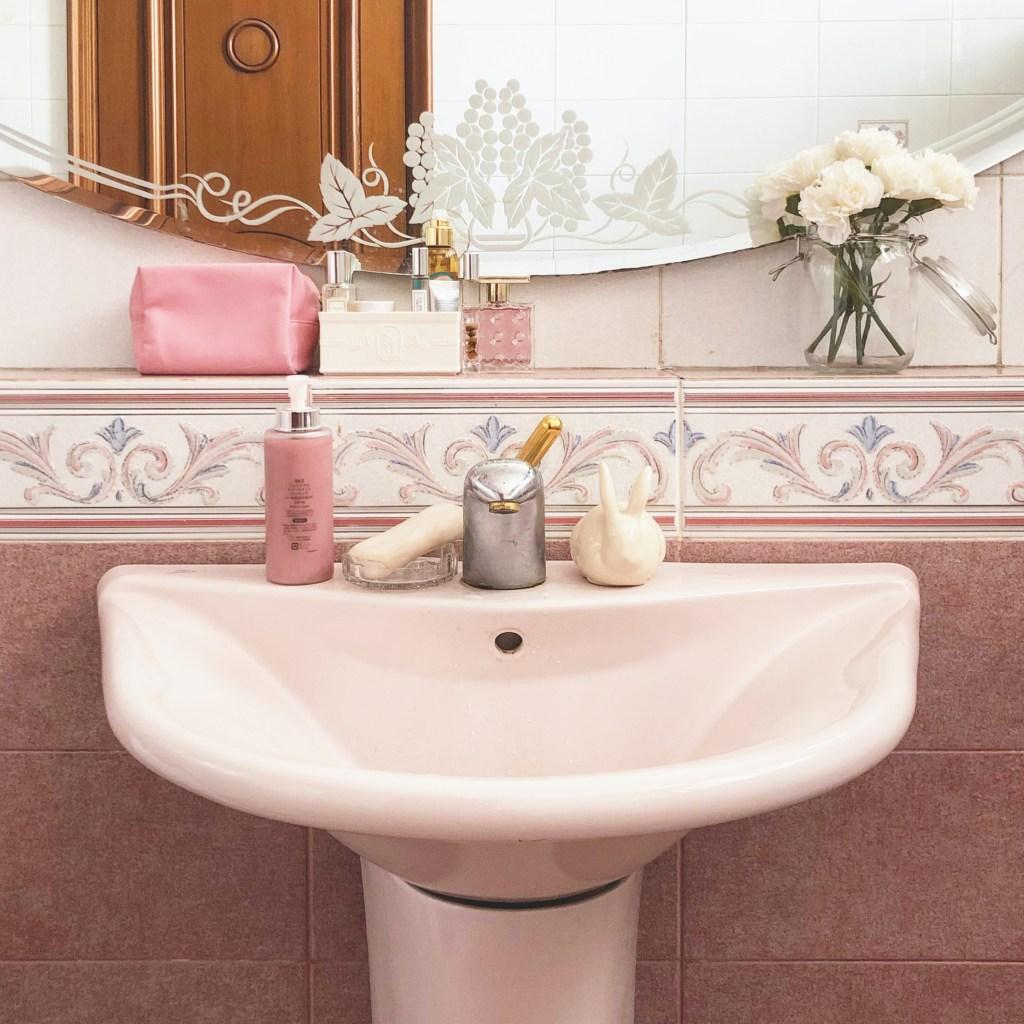 Pia rosa clara em parede de azuleijos rosa queimado. Sabonete rosa. Vasinho de flores brancas.