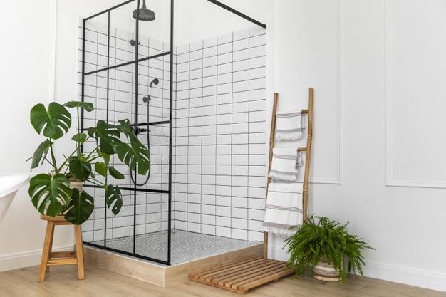 Banheiro branco com box de vidro com moldura preta. Banquinho com vaso de costela de adão.
