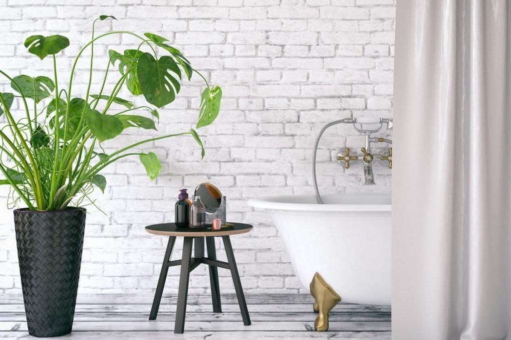 Banheiro com banheira, banquinho e vaso de planta. Parede de tijolinhos brancos