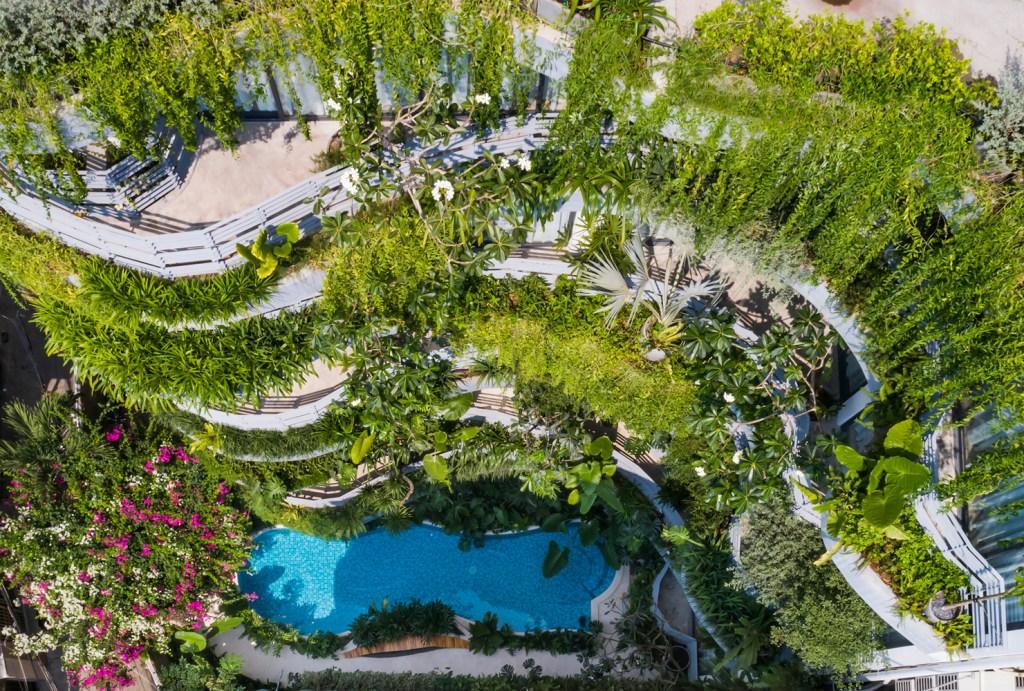 Visão de cima do prédio, onde é possível enxergar as plantas nas varandas dos apartamentos. No solo, uma piscina com linhas org´nicas na cor azul no centro da foto