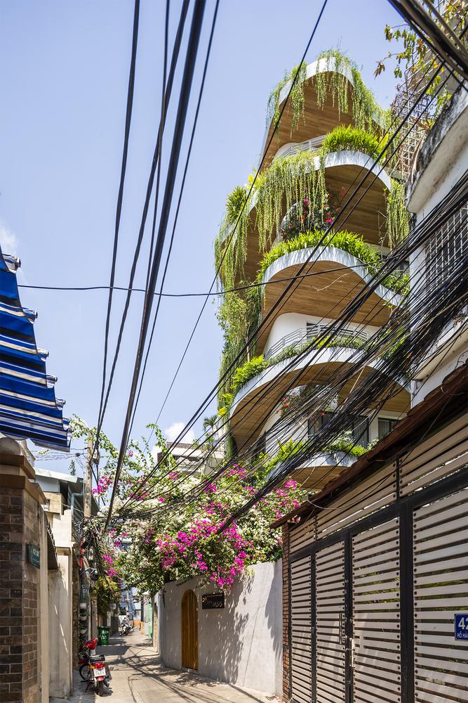 Visão da fachada, com prédios menores ao lado, com vista para as varandas com plantas tropicais no prédio branco e com detalhes em madeira clara